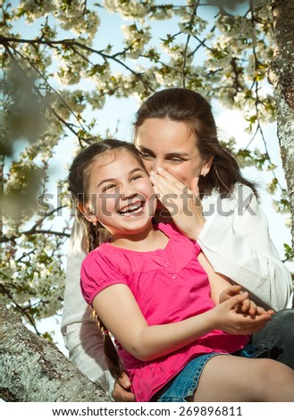 Cute little girl playing on tree in early spring  - stock photo