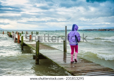 Cute little girl playing outdoors next to lake on a cold weather, back view - stock photo