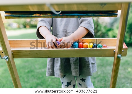 Cute little girl playing outside painting with colorful crayons