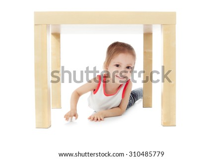 cute little girl playing under the table - stock photo