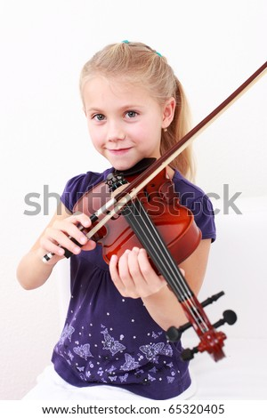Cute little girl playing violin - stock photo