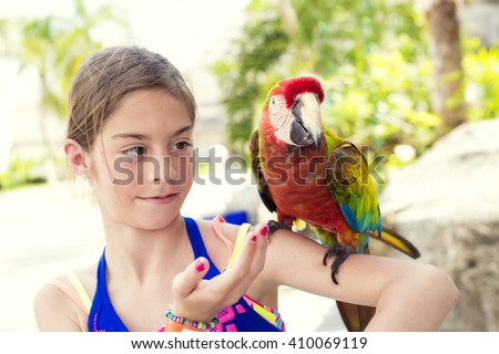 Cute little girl playing with a Scarlet Macaw Parrot while on cruise vacation in Mexico. - stock photo