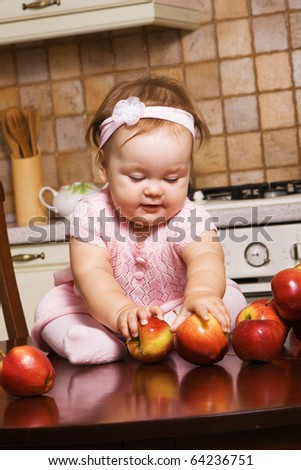 Cute little girl playing with apples on kitchen's table - stock photo