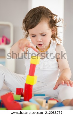 Cute little girl playing with building blocks on bed at home
