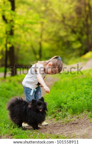 Cute little girl playing with dog in summer day - stock photo