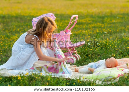 Cute little girl playing with her baby toy on the meadow on sunny summer day. - stock photo