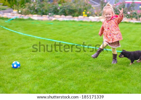 Cute little girl playing with her puppy in the yard - stock photo