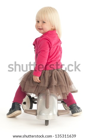 Cute little girl playing with her trike, while looking over her shoulder (isolated on white) - stock photo
