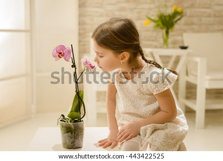 Cute little girl playing with orchid flowers, smelling them, indoor shot - stock photo