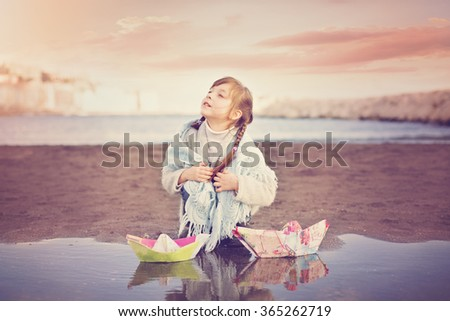 cute little girl playing with paper boat - stock photo