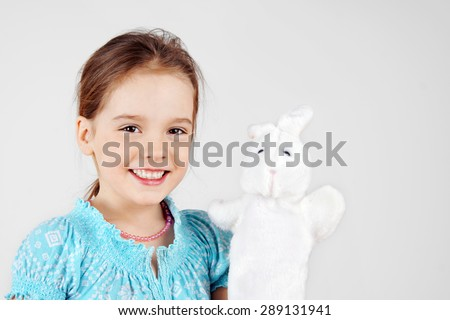 Cute little girl playing with rabbit hand puppet - stock photo
