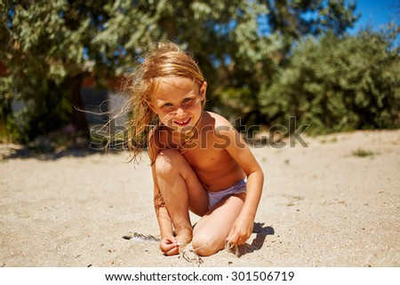 cute little girl playing with sand on the sunny beach - stock photo