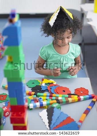 Cute little girl playing with shape puzzles in classroom - stock photo