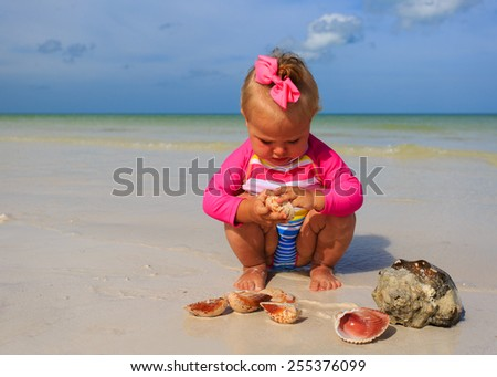 cute little girl playing with shells on summer beach - stock photo