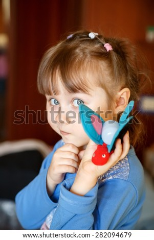 Cute little girl playing with toys and thinking - stock photo