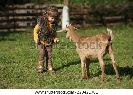 cute little girl plays with goat on the farm - stock photo