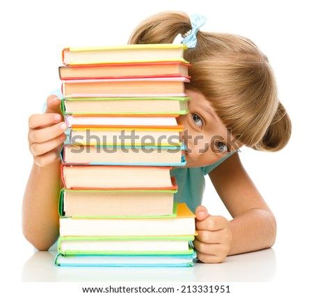 Cute little girl plays with pile of books while sitting at table, isolated over white - stock photo