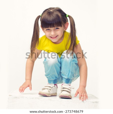 Cute little girl portrait in jeans  full length sit squat studio isolated on white - stock photo