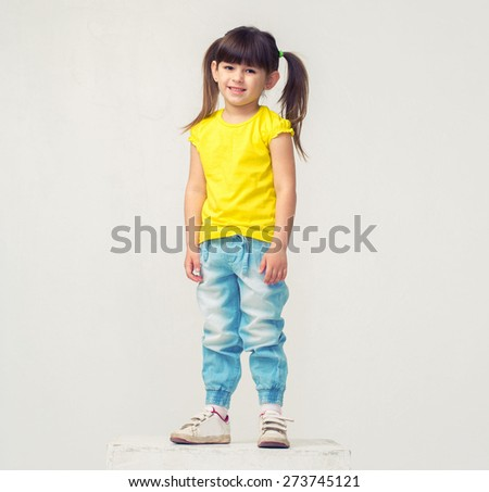 Cute little girl portrait in jeans full length stand studio isolated on white - stock photo
