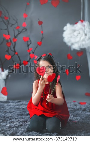 Cute little girl, posing for Valentine, hearts and decoration around her, smiling at the camera - stock photo