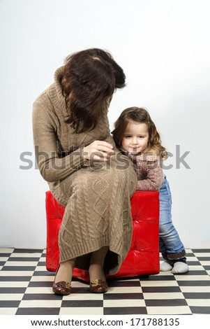Cute little girl posing in studio with her mother. White background - stock photo