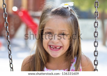 Cute little girl posing on the playground at bright summer day - stock photo