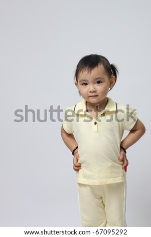 Cute little girl posing over gray background