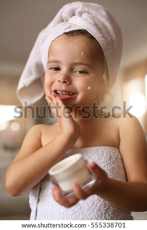 Cute little girl putting cream on her face. Looking at the camera.
