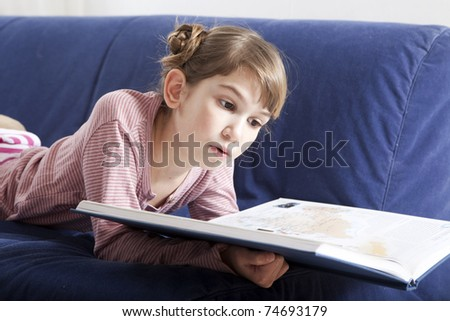Cute little girl reading a book - stock photo