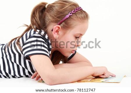 Cute little girl reading a book - stock photo
