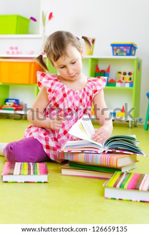 Cute little girl reading book on floor