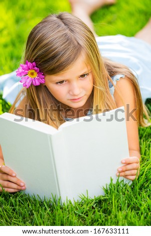 Cute little girl reading book outside on grass, relaxing outside in backyard - stock photo