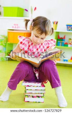 Cute little girl reading book sitting on stack of book - stock photo