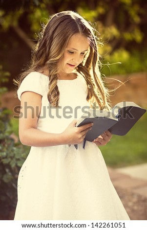 Cute little girl reading the Bible - stock photo