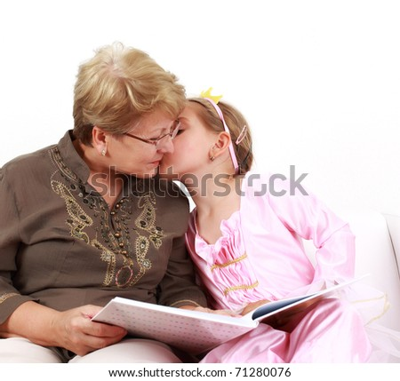 Cute little girl reading with grandmother and giving a kiss - stock photo