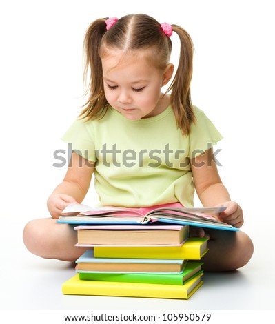 Cute little girl reads a book, isolated over white - stock photo