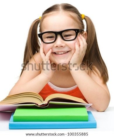Cute little girl reads a book while wearing glasses, isolated over white - stock photo