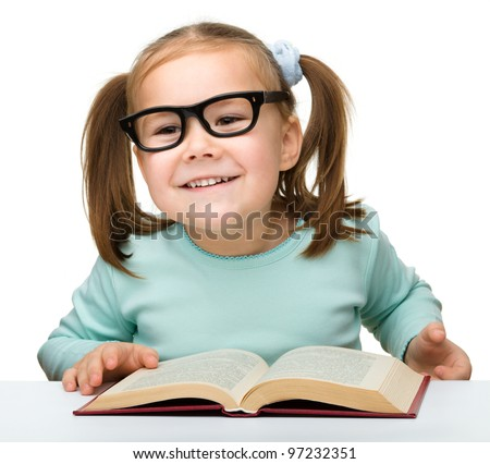 Cute little girl reads a book while wearing glasses, isolated over white