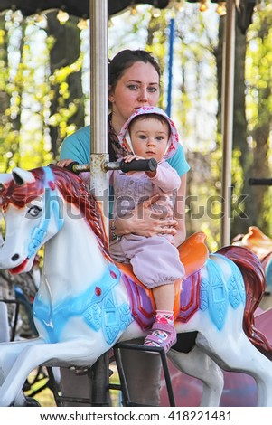 Cute little girl riding on a carousel horse with her mother, Europe. Family concept
