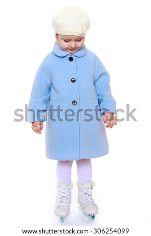 Cute little girl riding on figure skates. A girl stands awkwardly with his head down , which she shy-Isolated on white background - stock photo