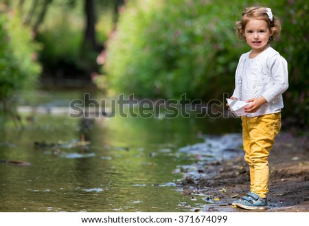 Cute little girl runs a paper boat in the stream in the park. Stretching her hand and reaching the little ship - stock photo