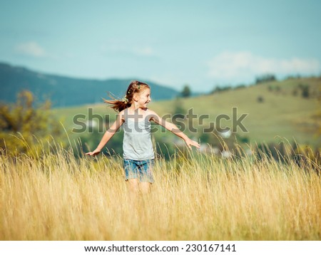 cute little girl runs through a beautiful meadow in the mountains. - stock photo