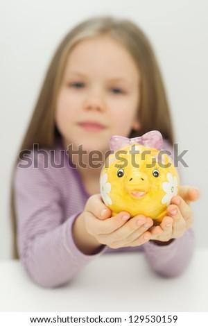 Cute little girl saving money in a piggy-bank - stock photo