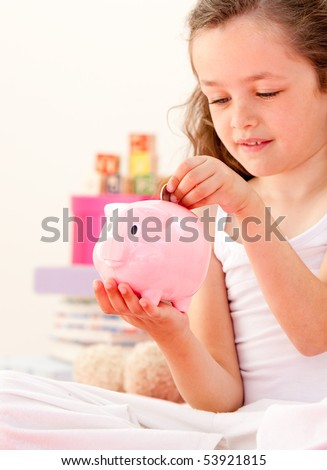 Cute little girl saving money in a piggy-bank sitting on her bed at home - stock photo
