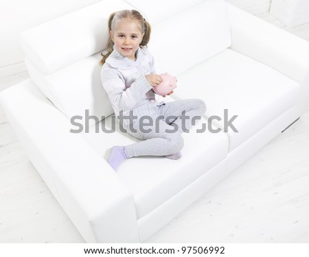 Cute little girl saving money in a piggy-bank sitting on sofa - stock photo