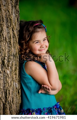 Cute little girl shone with happiness, curly hair, charming smile, sunny summer portrait