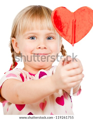 Cute little girl showing big red heart shaped lolly pop candy - stock photo