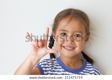 cute little girl showing I love you hand sign - stock photo