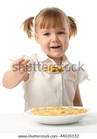 Cute little girl showing spoon filled with corn flakes, isolated over white