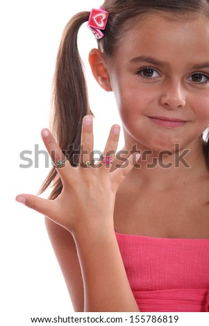 cute little girl showing the rings on her hand - stock photo